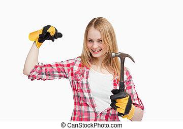 Joyful woman holding a hammer