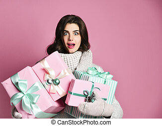 Joyful woman holding a lot of boxes with gifts on a pink background.