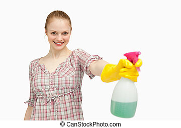 Joyful woman holding a spray bottle while smiling