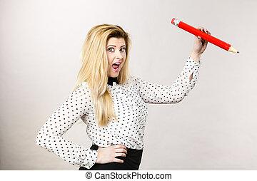 Joyful woman holds big pencil in hand
