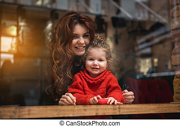 Joyful woman hugging child with love