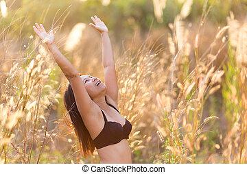Joyful woman in dry tropical meadow