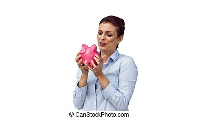 Joyful woman in slow motion kissing a piggy bank against a...
