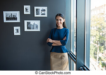 Joyful woman is posing near window