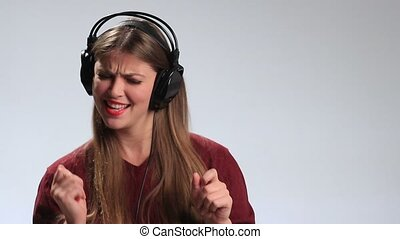 Joyful woman listening music in headphones