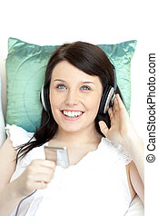 Joyful woman listening music lying on a sofa