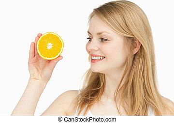 Joyful woman presenting an orange while looking at it