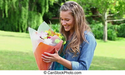 Joyful woman receiving a bunch of flowers