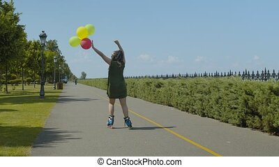 Back view of happy female in dress raising up hands holding colorful balloons while rollerblading along park alley. Positive carefree woman roller with afro-braids enjoying active summer leisure.