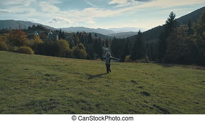 Joyful Woman Running Carpatian Mountain Valley. Happy Girl Enjoy on Green Highland Meadow. Ukraine Village Landscape. Female Tourist Moving with Raised Arms Up Panning Shot. Footage Shot in 4K