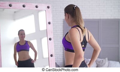 Joyful woman satisfied with reflection in mirror