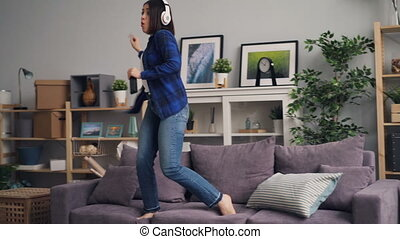 Joyful woman singing and dancing listening to music in headphones at home