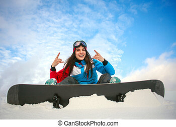 Joyful woman snowboarder sitting on top of mountain on blue sky
