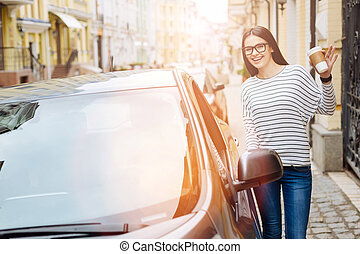 Joyful woman standing near car and waving at the camera
