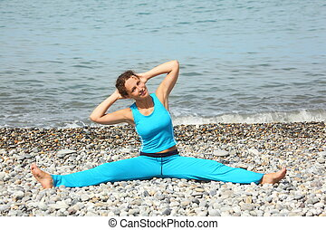joyful woman wearing sporty clothers is making exercise on sea coast. she is stretching