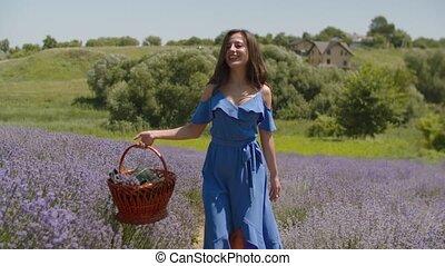 Joyful woman with arms outstretched walks in field - Joyful...