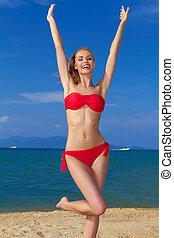 Joyful woman with arms raised - Joyful woman in red bikini ...