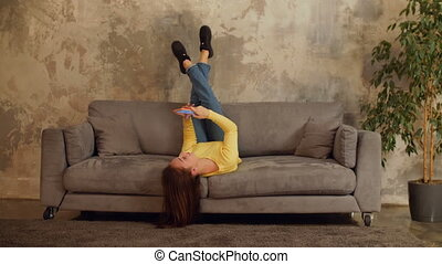 Joyful woman with cellphone relaxing on sofa