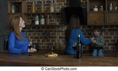 Joyful women chatting over red wine in the kitchen