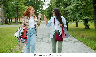 Joyful women friends are doing high-five walking in park with shopping bags laughing chatting enjoying warm autumn day. People and friendship concept.