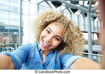 Joyful young african american woman taking selfie