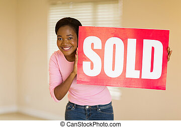 young african woman holding sold sign