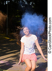 Joyful young asian woman jumping with Holi paint exploding around her