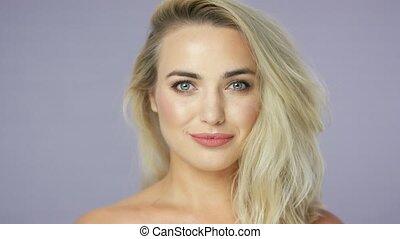 Joyful young blonde woman in studio