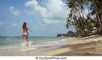 Joyful young brunette woman in bikini running along the exotic white sandy beach on sunny summer day and splashing sea waves in slow motion. 1920x1080