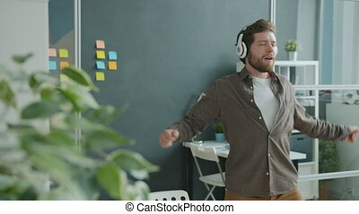 Joyful young businessman dancing in office listening to music through headphones