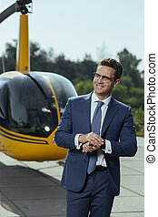 Joyful young businessman waiting for a helicopter pilot