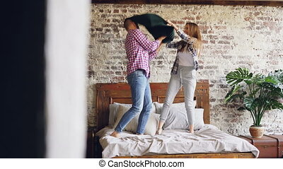 Joyful young couple is having pillow fight, having fun and laughing then hugging and kissing on double bed. Modern lifestyle and relationship concept.