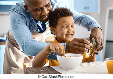 Joyful young father feeding cereals to toy of his son