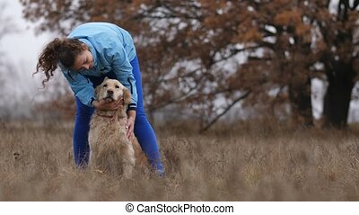 Joyful young female petting her lovely dog outdoors