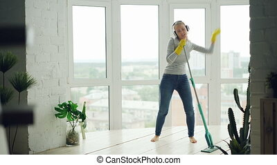 Joyful young lady is doing housework mopping floor and enjoying music in headphones, dancing and singing. Beautiful apartment with green plants is visible.