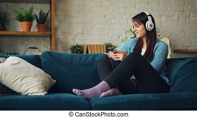 Joyful young lady is listening to music through headphones, using smartphone, smiling and laughing sitting on sofa at home enjoying rest and comfort.