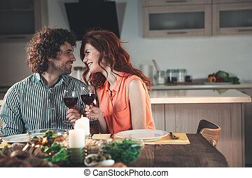 Joyful young man and woman celebrating anniversary at home