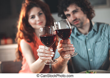 Joyful young man and woman celebrating with wineglasses