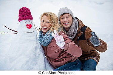 Joyful young man and woman having fun with snow in winter