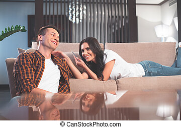 Joyful young man and woman using smartphone in apartment -...