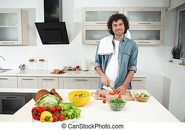 Joyful young man cutting vegetables in kitchen