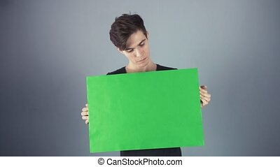 Joyful Young man in black shirt holding green key sheet poster gray background