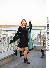 Joyful young model in coat posing at the square. Space for text