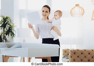 Joyful young mommy examining her notes