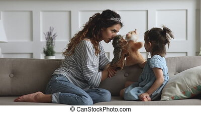 Joyful young mother wearing crowns with adorable preschool daughter, playing puppet toys, relaxing on cozy sofa. Happy attractive woman nanny babysitter enjoying free play time with kid girl.