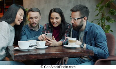 Joyful young people chatting and laughing having fun using smartphone in cafe