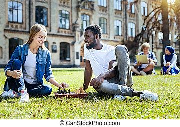 Joyful young people playing chess outdoors