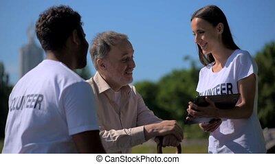 Joyful young volunteer using tablet with a senior man -...
