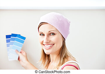 Joyful young woman choosing color for painting a room