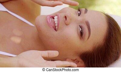 Joyful young woman having a spa treatment raising her hands...
